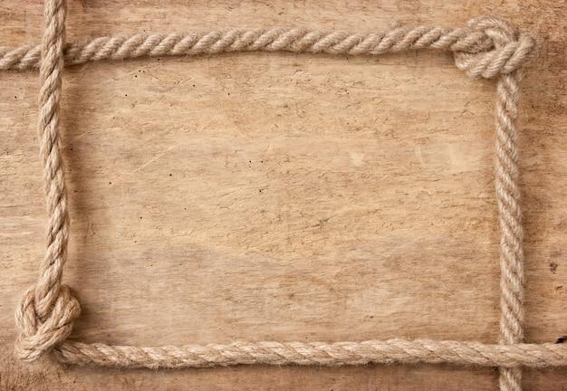 Rahmen aus seil auf einem hölzernen hintergrund