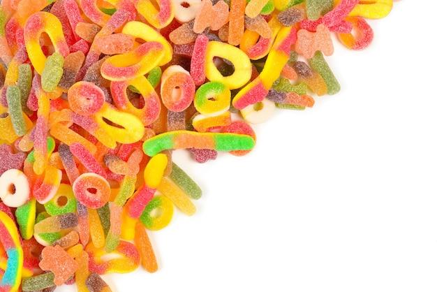 Rahmen aus verschiedenen gummiartigen bonbons, isoliert auf weiss. ansicht von oben. platz für text oder design.