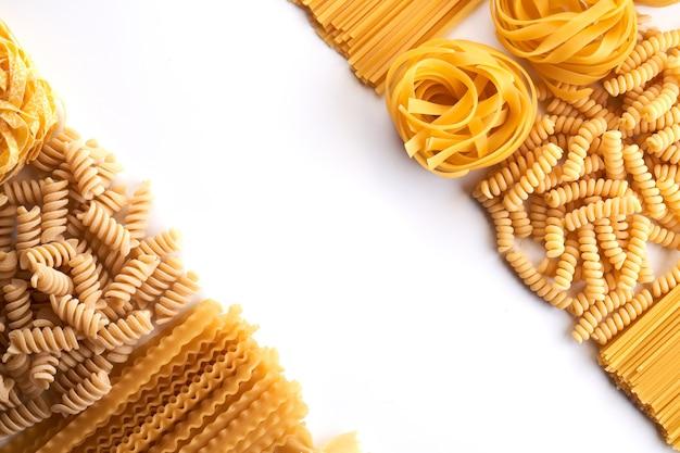 Rahmen aus verschiedenen sorten von nudeltapeten. mischen sie makkaroni, spaghetti auf weißem hintergrund mit kopierraum