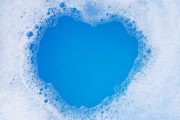 Rahmen aus waschmittelschaumblase. blauer hintergrund. herzform