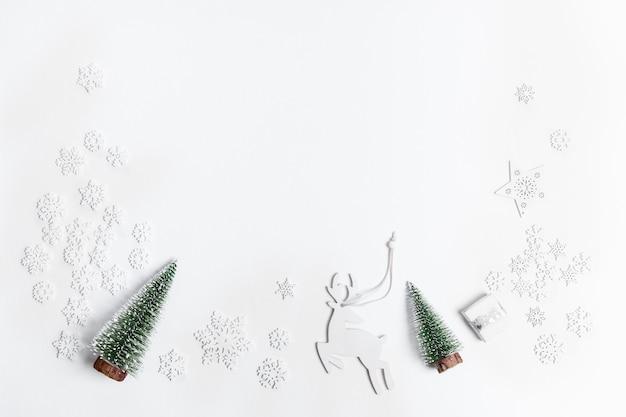 Rahmen aus weihnachtlichen weißen dekorationen schneeflocken und hirsche und zwei weihnachtsbäume auf weiß