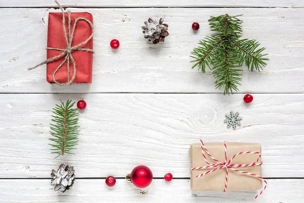 Rahmen aus weihnachtsgeschenk, tannenzapfen, tannenzweigen, roter kugel und beeren