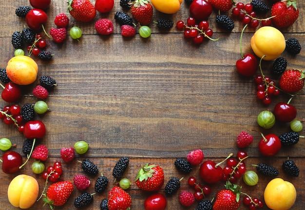 Rahmen der frischen und saftigen früchte auf hölzernem hintergrund