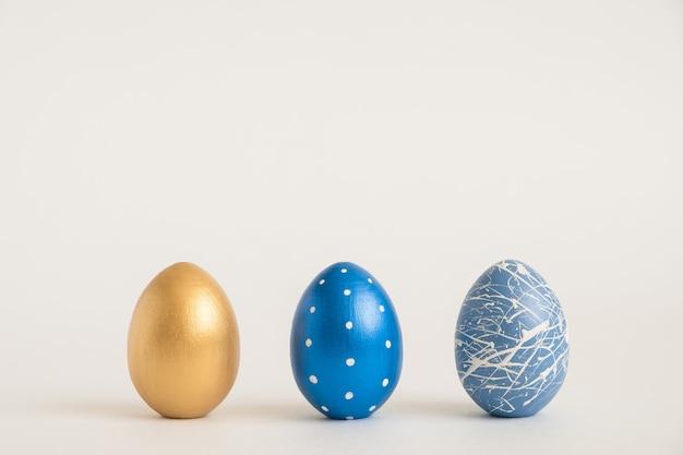 Rahmen der goldenen geschmückten ostereier im nest lokalisiert auf weißer oberfläche. minimales osterkonzept.