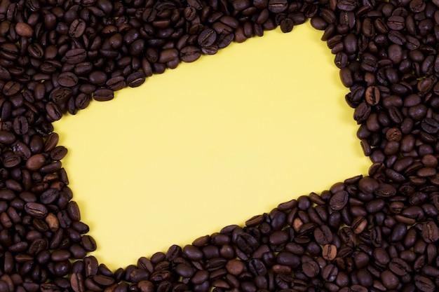 Rahmen der kaffeebohnen. gelber hintergrund