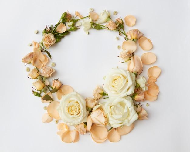 Rahmen der rosen über weißem hintergrund. schöne verzierung der rosen