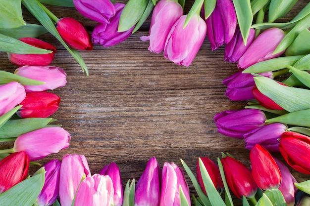 Rahmen der roten, rosa und lila tulpenblumen auf hölzernem hintergrund