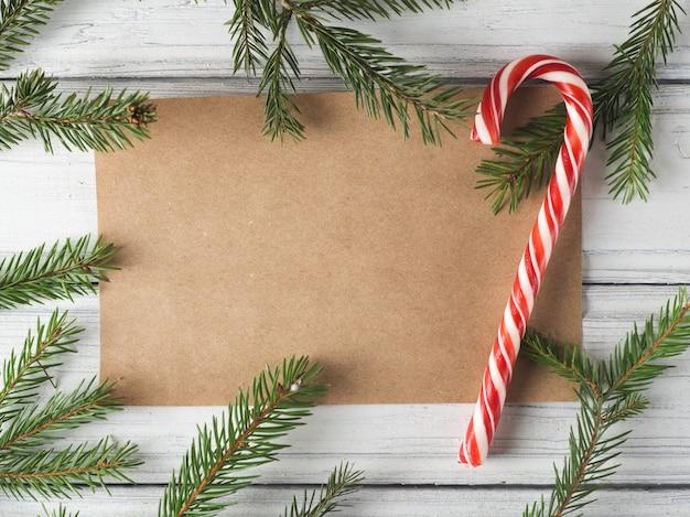 Rahmen der zweige der weihnachtsbaum und kraftpapier blatt nach der mitte