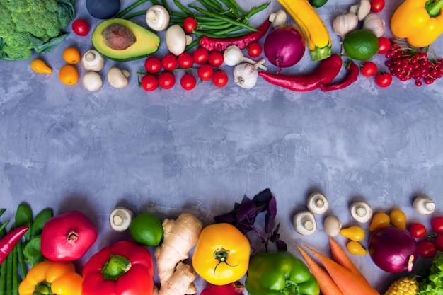 Rahmen des gesunden bunten würzigen gewürzten gewürzes mit frischem sommer-bio-antioxidansfrüchten und -gemüse für veganes oder vegetarisches menü lokalisiert auf grauem hintergrund. gesundes lebensstilkonzept