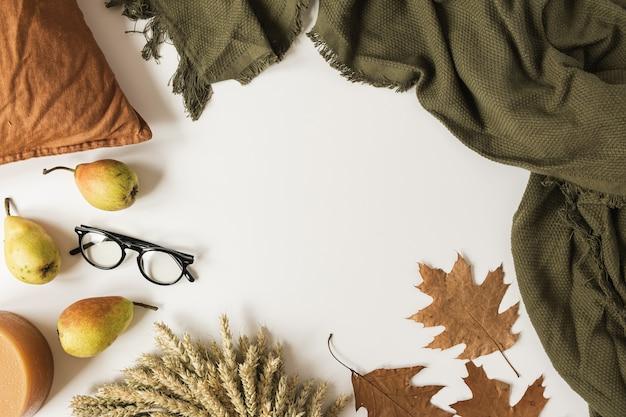 Rahmen des herbstlichen weißen tisches mit decke, kissen, gläsern, trockenem herbstlaub, birnen, kranz aus weizenstroh.
