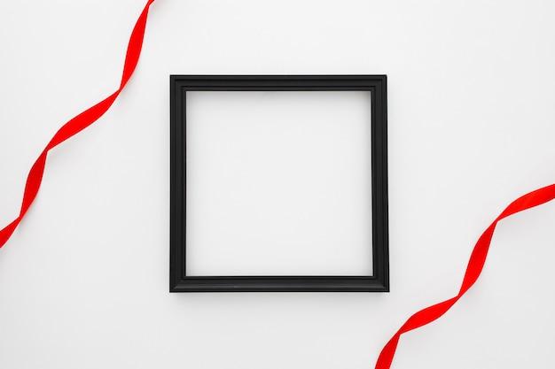 Rahmen des schwarzen quadrats mit roter bindung zwei auf weißem hintergrund