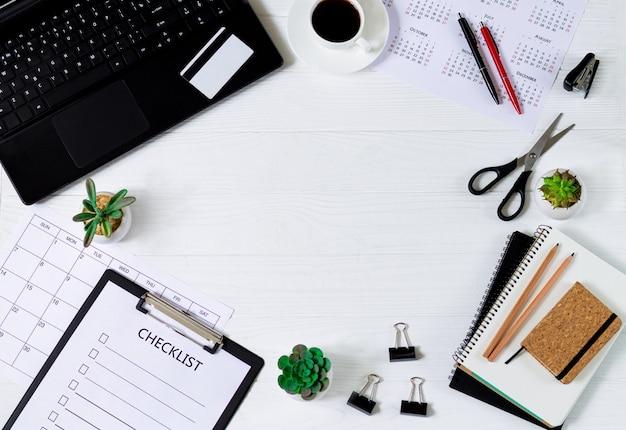 Rahmen des weißen hölzernen büroschreibtisch-tischhintergrunds mit laptop und zubehör