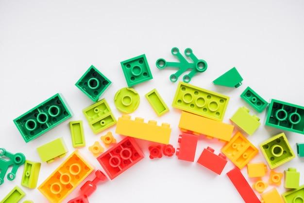 Rahmen für kinderspiele entwickeln. bunte plastiksteine und -blöcke auf weißem hintergrund, draufsicht, raum für text. lernspielzeug für kinder.