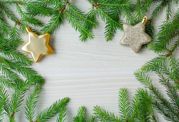 Rahmen für weihnachtsfichtenzweige mit sternspielzeug und copyspace