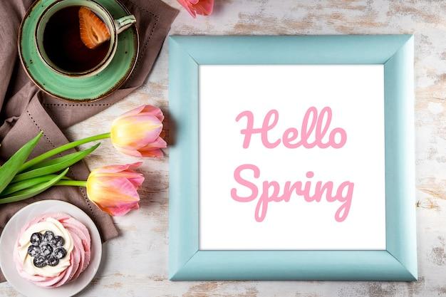 Rahmen mit der aufschrift hallo frühling, rosa tulpen, kuchen und eine kappe des tees auf einem weißen hölzernen hintergrund. hochwertiges foto