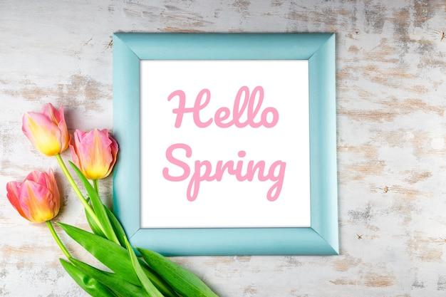 Rahmen mit der aufschrift hallo frühling und rosa tulpen auf einem weißen hölzernen hintergrund. hochwertiges foto