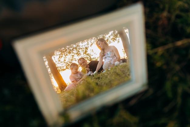 Rahmen mit familienfoto auf gras
