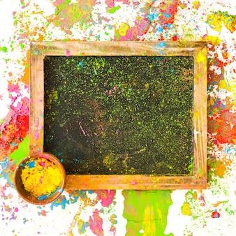 Rahmen mit farbe in einer kleinen schüssel zwischen hellen, trockenen farben