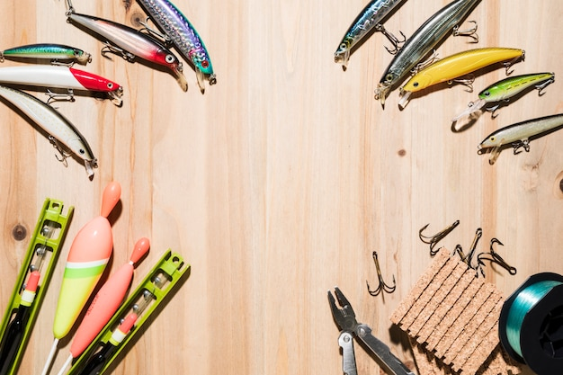 Rahmen mit fischköder gemacht; fischenfloss; zange; haken auf hölzernen hintergrund