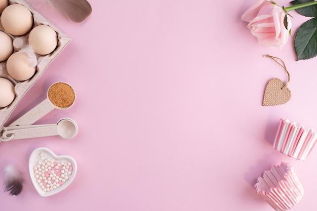 Rahmen mit lebensmittelzutaten zum backen auf einem sanft rosa pastelltisch. koch flach lag mit kopierraum. draufsicht. backkonzept. flach liegen
