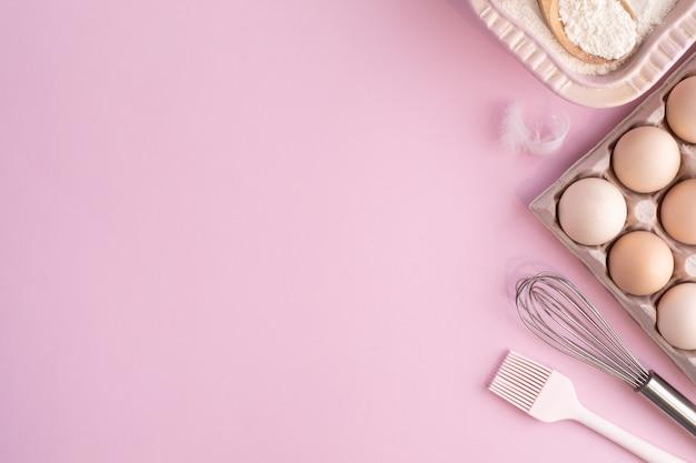 Rahmen mit lebensmittelzutaten zum backen auf einer sanft rosa pastelloberfläche