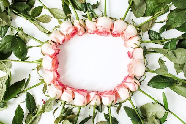 Rahmen mit leerem kopierraummodell aus rosa rosenblüten auf weißer oberfläche