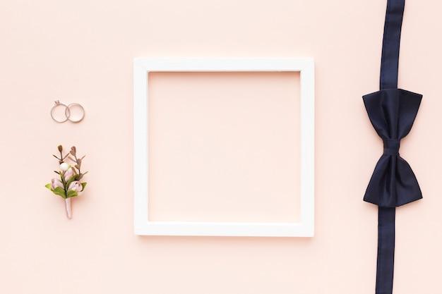Rahmen mit schleife und verlobungsringen auf dem tisch