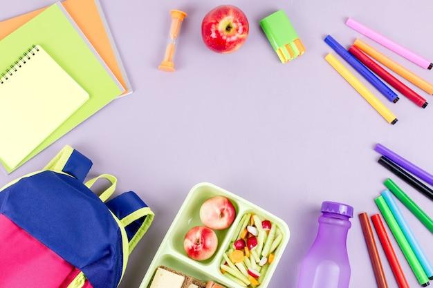 Rahmen mit schulmaterial für kinder auf lila tischplatte