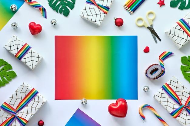 Rahmen mit weihnachtsdekor und geschenken mit regenbogenband in den lgbtq-gemeinschaftsflaggenfarben
