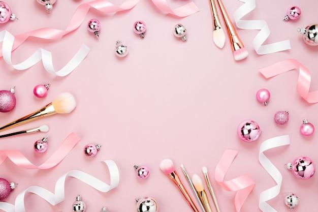 Rahmen mit weihnachtskugel, band, make-up-pinsel und dekorationen in pastellrosa. urlaub-hintergrund. schönheitskonzept. flache lage, ansicht von oben