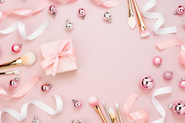 Rahmen mit weihnachtskugel, geschenk, band, kosmetik und dekorationen in pastellrosa. urlaub-hintergrund. schönheitskonzept. flache lage, ansicht von oben