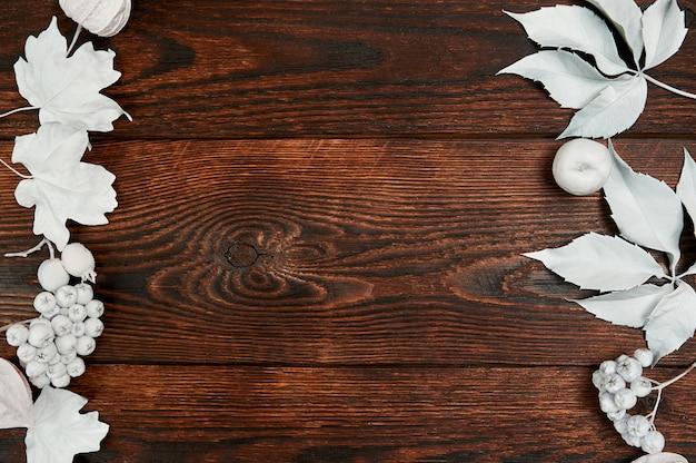 Rahmen mit weißen blättern auf dunkelbraunem holzhintergrund, flach gelegtes modell für ihre kunst, ihr bild oder ihre handbeschriftung.
