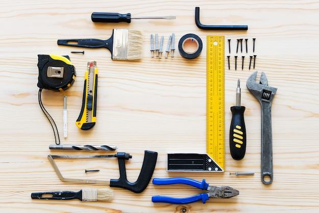 Rahmen oder zusammensetzung von bauwerkzeugen für den bau einer haus- oder wohnungserneuerung, auf einem holztisch. der arbeitsplatz des vorarbeiters. das thema zu hause und professionelle reparatur, bau.
