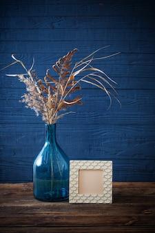 Rahmen und getrocknete blumen in der blauen glasvase auf altem holztisch