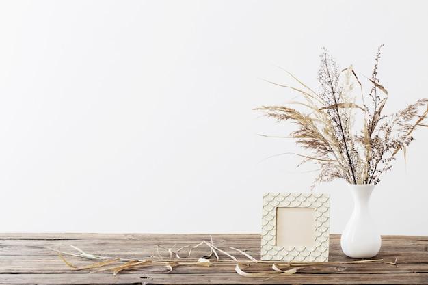 Rahmen und getrocknete blumen in der weißen vase auf altem holzregal