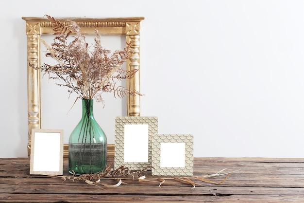 Rahmen und getrocknete blumen in grüner vase auf altem holzregal