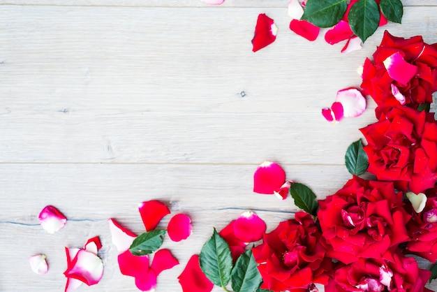 Rahmen von den rosen auf grauem hölzernem hintergrund.