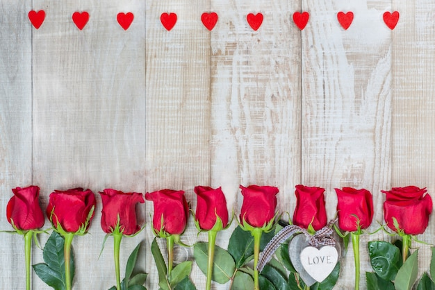 Rahmen von herzen und rosen auf einer hellen holzoberfläche.