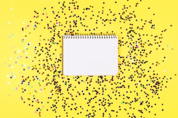 Rahmen von leuchtenden bunten sternen mit leerem notizbuch auf gelbem hintergrund