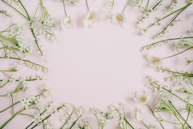 Rahmen von maiglöckchen, grüne blätter auf rosa