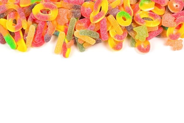 Rahmen von verschiedenen gummiartigen bonbons lokalisiert auf weiß. draufsicht. platz für text oder design.