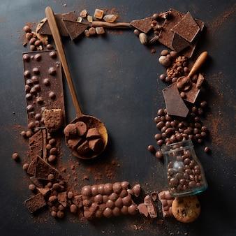 Rahmen von verschiedenen pralinen und kakaopulver auf einem dunklen hintergrund