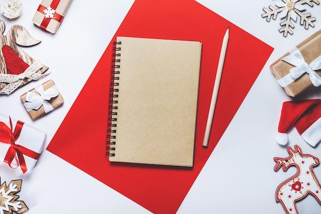Rahmen von weihnachtsbaumspielzeug und geschenkboxen mit geöffnetem leerem notizbuch in der mitte