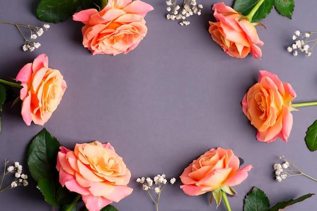 Rahmenkarte vom natürlichen blumenstrauß der frisch gepflückten rosenblumen auf einem pastellrosa hintergrund.