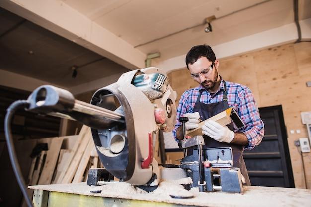 Rahmenunternehmer mit einer kreissäge abschneiden, um holzbolzen auf länge zu schneiden