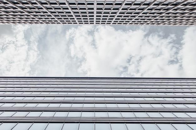 Rahmung mit der fassade des bürogebäudes schuss von unten nach oben mit einem horizontalen streifen von grauem himmel mit wolken. business center an einem wolkigen tag