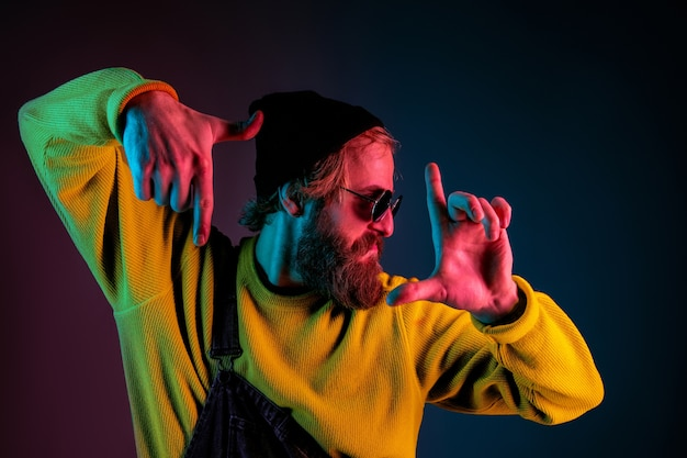 Rahmung, selfie. porträt des kaukasischen mannes auf gradientenraum im neonlicht