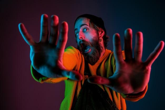 Rahmung, selfie. porträt des kaukasischen mannes auf gradientenstudiohintergrund im neonlicht. schönes männliches modell mit hipster-stil. konzept der menschlichen emotionen, gesichtsausdruck, verkauf, anzeige.