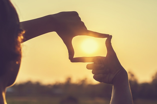 Rahmungsansicht der hand entfernt über sonnenuntergang