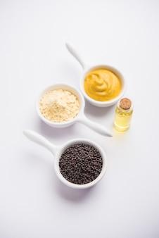 Rai oder roher senf mit sauce, pulver und öl über stimmungsvollem hintergrund. selektiver fokus